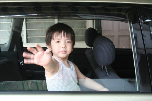 boy waving in the car